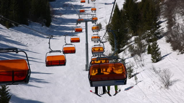 beautiful shot of people in ski lifts over snowy landscape on sunny day - park city, utah - park city stock videos & royalty-free footage