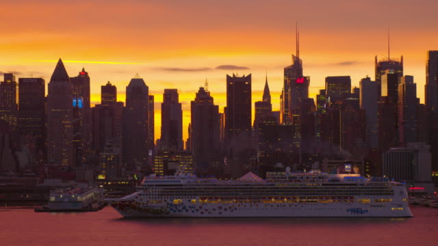 Beautiful shot of the Manhattan Skyline against a orange and blue sky during sunset, shot from across the Hudson River. The Norwegian Gem Cruise Ship can be seen going along the Hudson River against a beautiful orange and blue sky