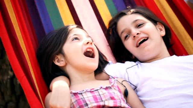 bella sorella rilassarsi insieme in un'amaca - meraviglie della natura video stock e b–roll