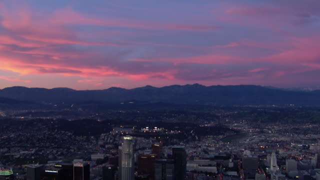 Beautiful sky at twilight over the Santa Monica Mountains and tilt down to reveal the city of Los Angeles.