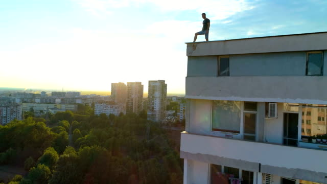 Beautiful slow motion ascending drone shot revealing man standing on a builging edge at sunset
