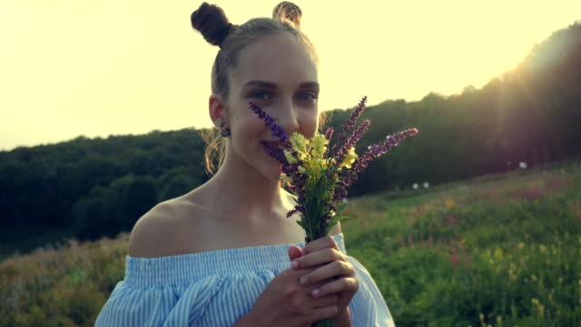 beautiful smiling girl standing in a countryside with a bouquet of field flowers in hands at golden sunset - girls wearing see through clothes stock videos and b-roll footage