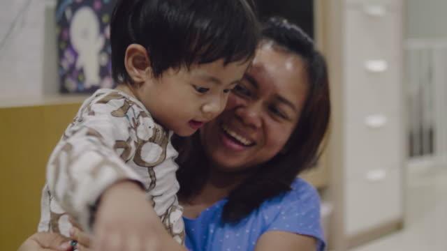 vídeos de stock e filmes b-roll de beautiful smiling mom and happy baby together - edifício de infantário