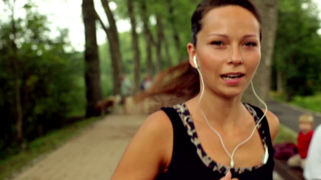 Beautiful, smiling woman running in the park.