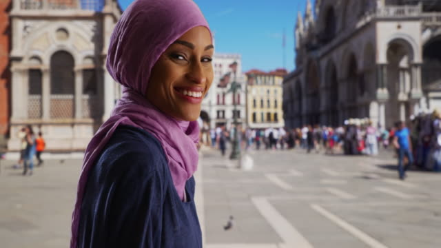 beautiful smiling young muslim woman sightseeing in venice, italy - modest clothing stock videos & royalty-free footage