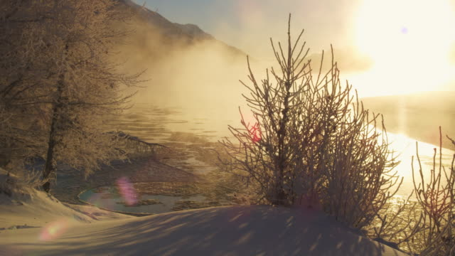 stockvideo's en b-roll-footage met beautiful snow scene of chilkat river with ice and mist rising backlit - meer dan 50 seconden