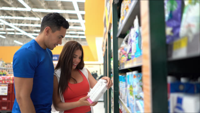 beautiful sports couple at a supermarket reading the label on a milk box while talking - milk box stock videos & royalty-free footage