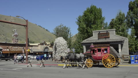 stockvideo's en b-roll-footage met ms beautiful stage coach rides in downtown center / jackson hole, wyoming, united states - wyoming