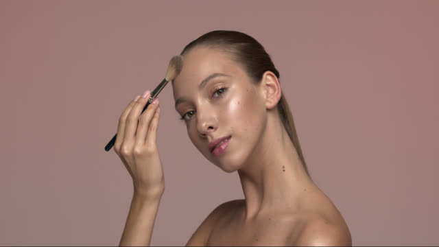 vídeos de stock e filmes b-roll de a beautiful stately girl with green eyes completes her daytime make-up with a highlighter brush. - cabelo natural
