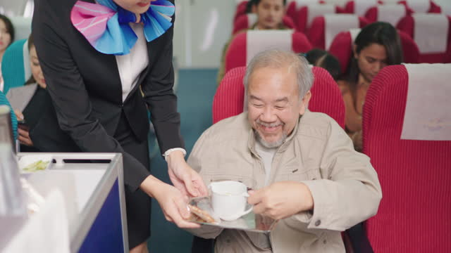 beautiful stewardess offering drink and snacks to old man passenger in jet . - cart stock videos & royalty-free footage