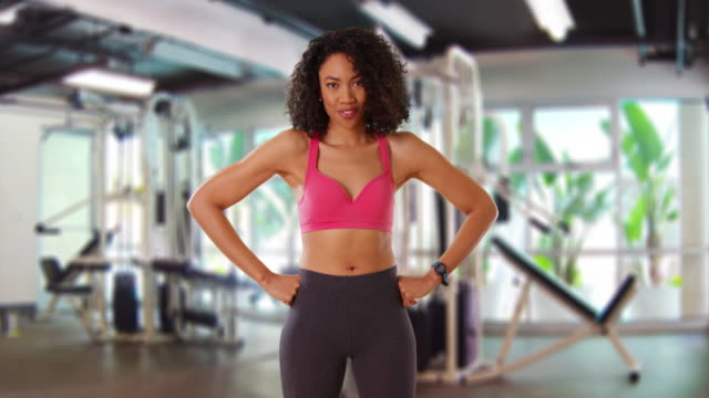 beautiful, strong black woman flexing her muscles at gym, laughing - flexing muscles stock videos & royalty-free footage