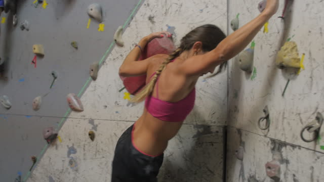 beautiful strong fit woman climbing up a wall looking very focused - climbing wall stock videos & royalty-free footage