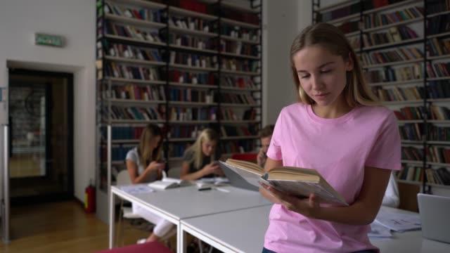 Schöne Schüler lesen ein Buch über den Vordergrund und andere Schüler im Hintergrund Chatten auf Smartphones