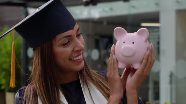 beautiful student wearing a graduation cap and gown holding a pink piggy bank looking at camera smiling - savings stock videos & royalty-free footage