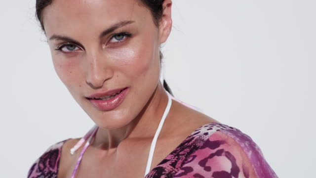 beautiful summery model with glowing skin comes into frame and looks at camera - bikini top stock videos & royalty-free footage