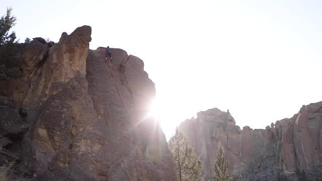 vídeos de stock e filmes b-roll de beautiful sun flare and climber descending cliff face in smith rock, oregon - outdoor pursuit