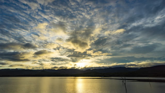beautiful sunrise over mountains and lake, day to sunset time lapse - tree trunk stock videos & royalty-free footage