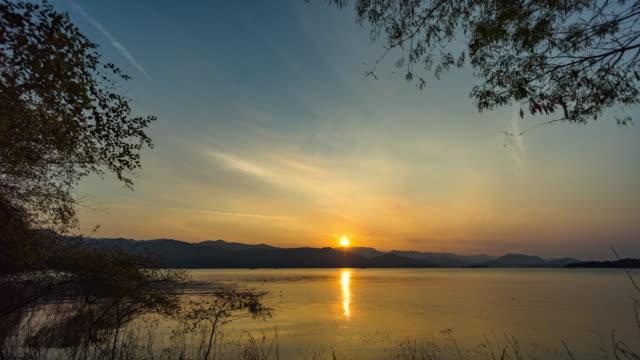 vídeos de stock, filmes e b-roll de nascer do sol bonito sobre montanhas e lago, vídeo do lapso de tempo - floresta tropical