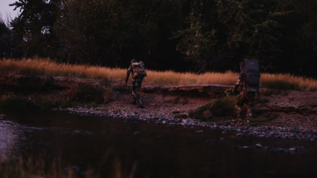 a beautiful sunset dances off the river as two hunters quickly stalk an animal just after dark in light. - military school stock videos and b-roll footage