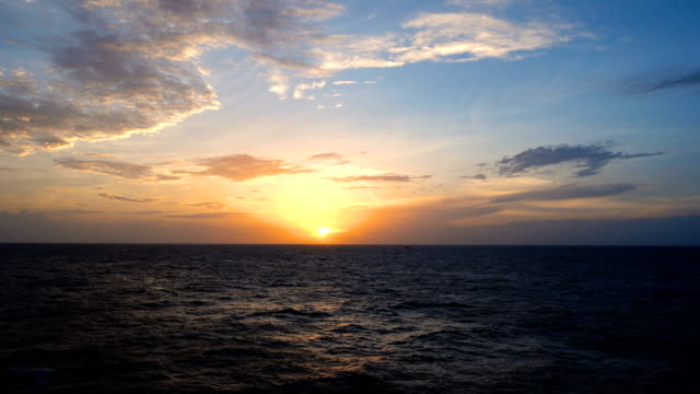 stockvideo's en b-roll-footage met prachtige zonsondergang in offshore, amazing kleuren, lichtschermbewaking cat.2 schijnt door de cloudscape - horizon over water
