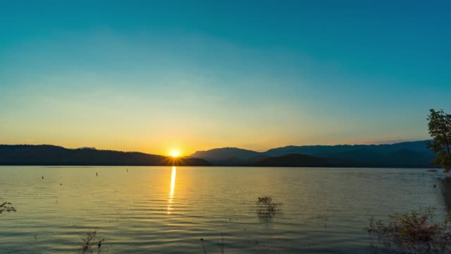 beautiful sunset over mountains and lake, day to sunset time lapse - tree trunk stock videos & royalty-free footage