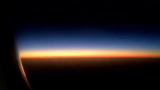 vídeos de stock, filmes e b-roll de belo pôr do sol através da janela do avião - horizonte
