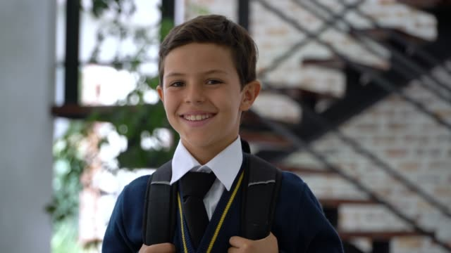 beautiful sweet little boy in school uniform carrying his backpack and smiling at camera - schoolboy stock videos and b-roll footage