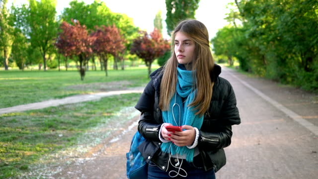 beautiful teenage girl in the city park text messaging - bullying stock videos & royalty-free footage