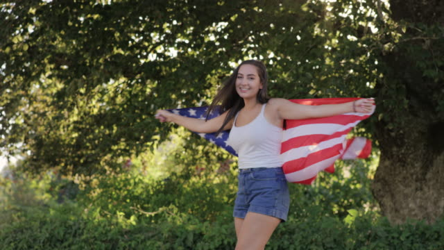 beautiful teenage girl spinning around laughing with american flag - 14 15 years stock videos and b-roll footage