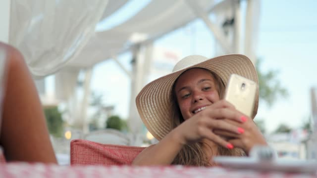 beautiful teenage girl taking selfie while sitting in restaurant on summer vacation with sun hat on - seductive women stock videos & royalty-free footage