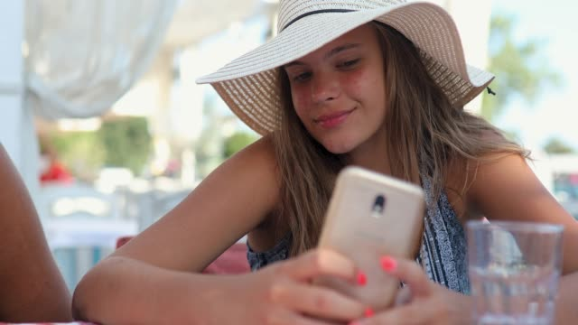 vídeos de stock e filmes b-roll de beautiful teenage girl taking selfie while sitting in restaurant on summer vacation with sun hat on - técnica de iluminação