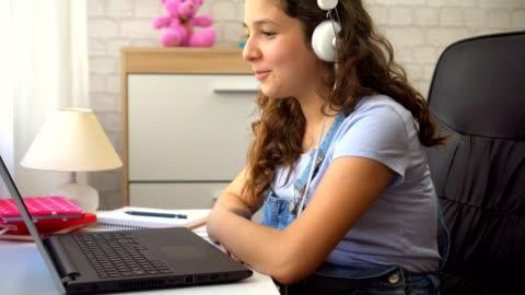 vacker tonårsflicka med hörlurar använder en bärbar dator - hörlurar bildbanksvideor och videomaterial från bakom kulisserna