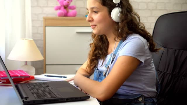beautiful teenage girl with headphones using a laptop - e learning stock videos & royalty-free footage