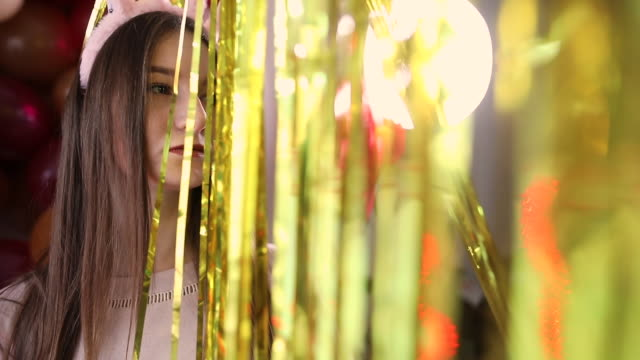 beautiful teenage girl with rabbit ears costume behind gold colored metallic foil curtain on party - rabbit costume stock videos & royalty-free footage
