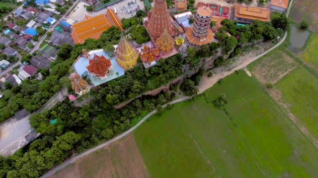 Beautiful temple and golden Buddha on the top of mountain among uncultivated rice paddy, aerial video