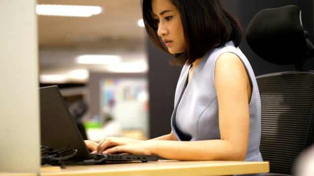Beautiful Thai business woman is using computer laptop for working with concentrate emotion at the office -smart officer woman in the office