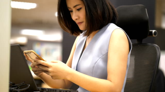 Beautiful Thai business woman is using smart phone and computer laptop for working with concentrate emotion at the office -smart officer woman in the office