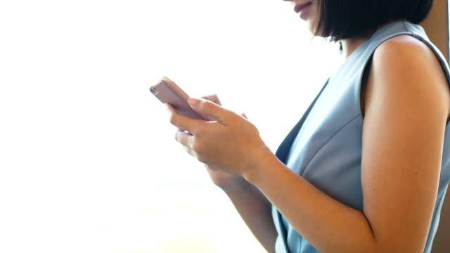 vídeos y material grabado en eventos de stock de hermosa empresaria tailandesa está utilizando smartphone para trabajar con el concepto de mujer de negocios inteligente emoción positiva - concentración