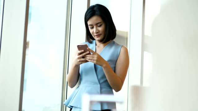 Beautiful Thai business woman is using smartphone for working with positive emotion-smart business woman concept