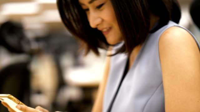 Schöne Thai Offizier Frau nutzt Smartphone für für die Aufnahme eine Pause-Offizier Tag Lebenskonzept