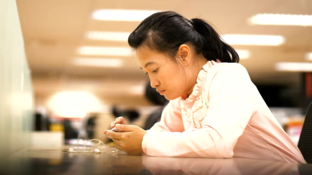 Beautiful Thai officer woman is using smartphone for for taking a break-officer day life concept