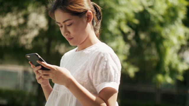 vídeos de stock, filmes e b-roll de linda mulher tailandesa está usando o telefone inteligente no jardim - voz
