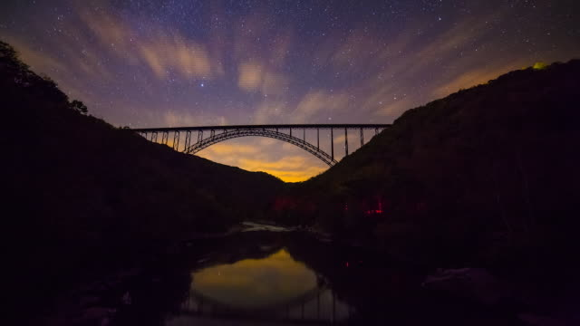 beautiful time lapse shot showing the stars moving above the new river gorge bridge in west virginia. - constellation stock videos & royalty-free footage