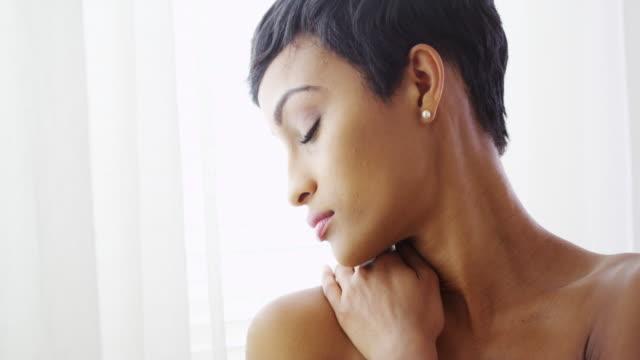 vídeos y material grabado en eventos de stock de beautiful topless black woman hugging herself and looking out window - articulación humana