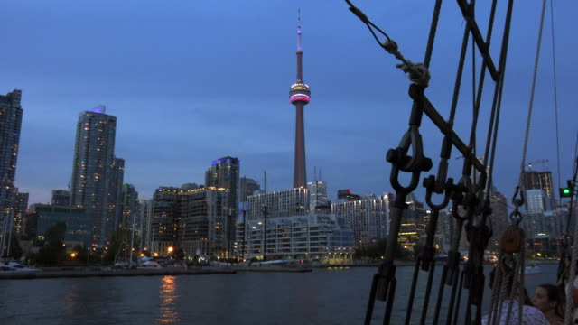 Beautiful Toronto skyline and CN tower at dusk from a sail cruise ship Cruises in Lake Ontario are a very popular tourist attraction in the Canadian...