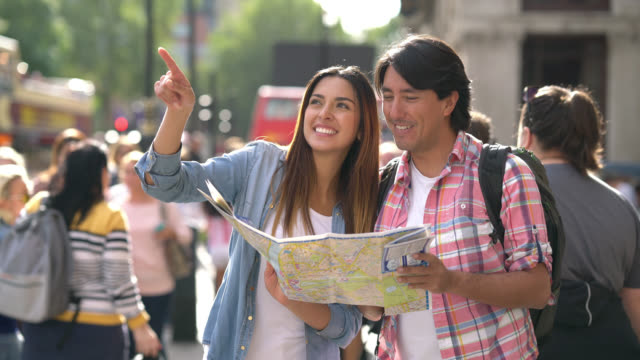 beautiful tourist couple sightseeing and looking at a map - tourist stock videos & royalty-free footage