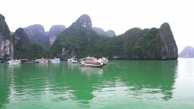 vídeos de stock, filmes e b-roll de o navio de cruzeiros bonito do turista está movendo entre rochas da pedra calcária na baía de ha long, vietnam - ilha