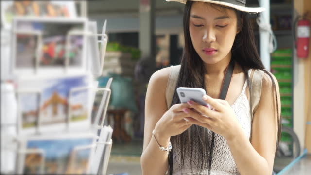 美しい観光客、美しい女性は、製品を買い物し、カードを投稿します。観光客はダムンサドゥアクの水上市場、バンコク、タイで旅行します。 - ギフトショップ点の映像素材/bロール