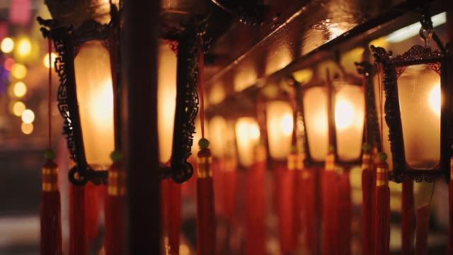 beautiful traditional chinese lanterns glowing in lights hanging inside man mo temple in hong kong - closeup shot - ハリウッドロード点の映像素材/bロール