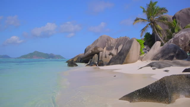 beautiful tropical beach anse source d´argent with sculpted granite rocks and palm trees - island of la digue, seychelles, indian ocean islands. - seychelles stock videos & royalty-free footage